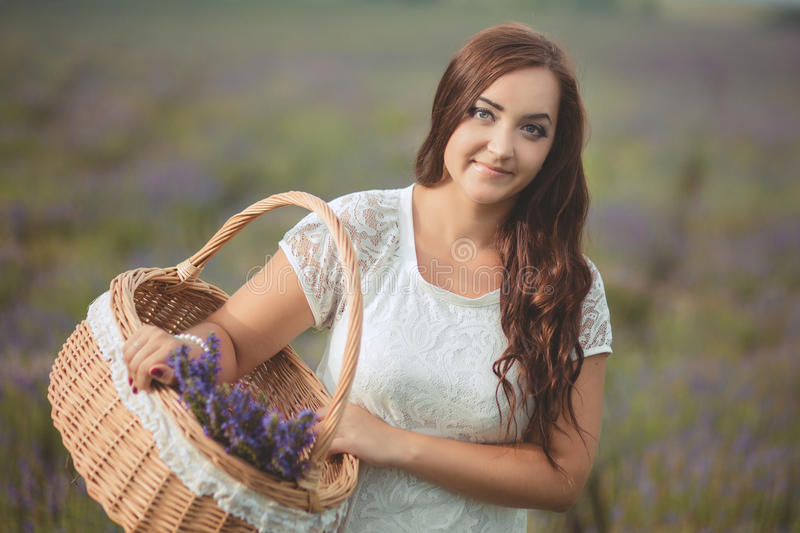 Beautiful provence woman relaxing in lavender field watching on sunset holding basket with lavanda flowers. Series. alluring girl royalty free stock photos