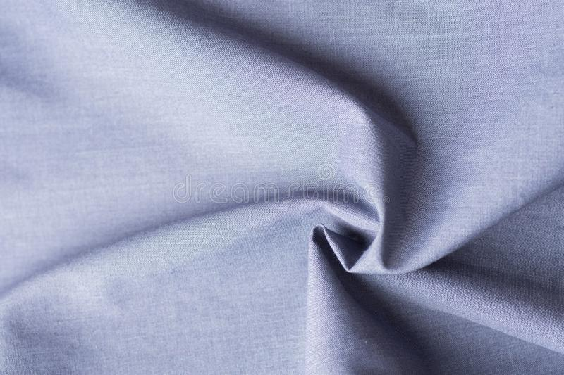 Beautiful pure organic cotton fabric laid out in concentric spiral pattern. Elegant blue gray pastel color. Sewing stock photography