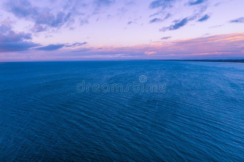 Purple dusk over calm ocean. Beautiful purple dusk over calm ocean coastline - aerial view royalty free stock photos