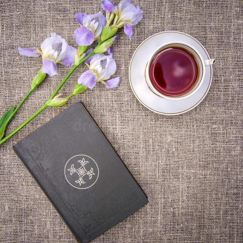 Beautiful purple flowers irises, book and a cup of tea on a canvas background. Beautiful purple flowers irises, old book and a cup of tea on a gray canvas royalty free stock image
