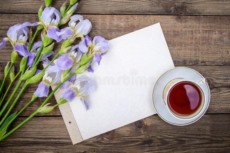 Beautiful purple flowers irises, a sheet of paper and a cup of tea on a wooden background. Beautiful purple flowers irises, a sheet of paper and a cup of tea on royalty free stock photos