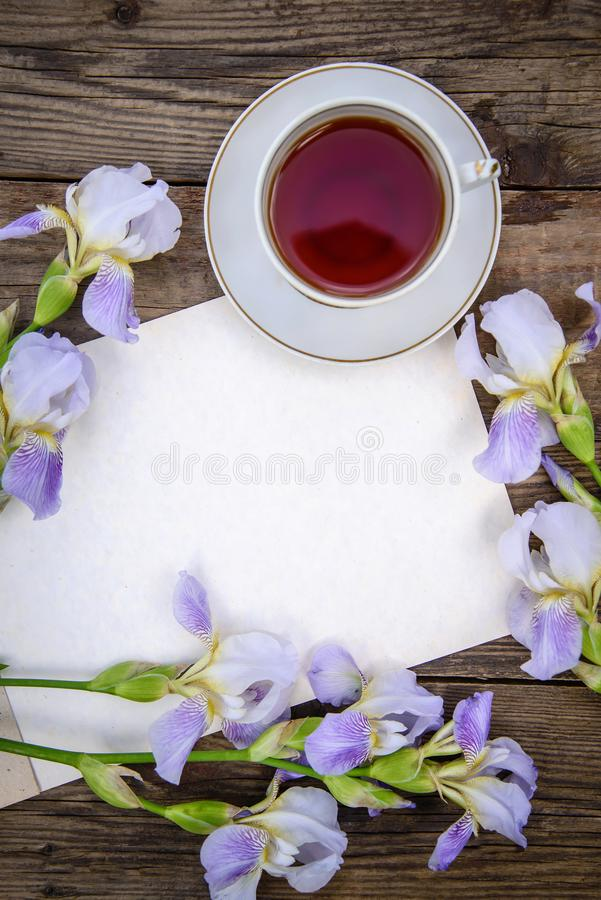 Beautiful purple flowers irises, a sheet of paper and a cup of tea on a wooden background. Beautiful purple flowers irises, a sheet of paper and a cup of tea on royalty free stock image