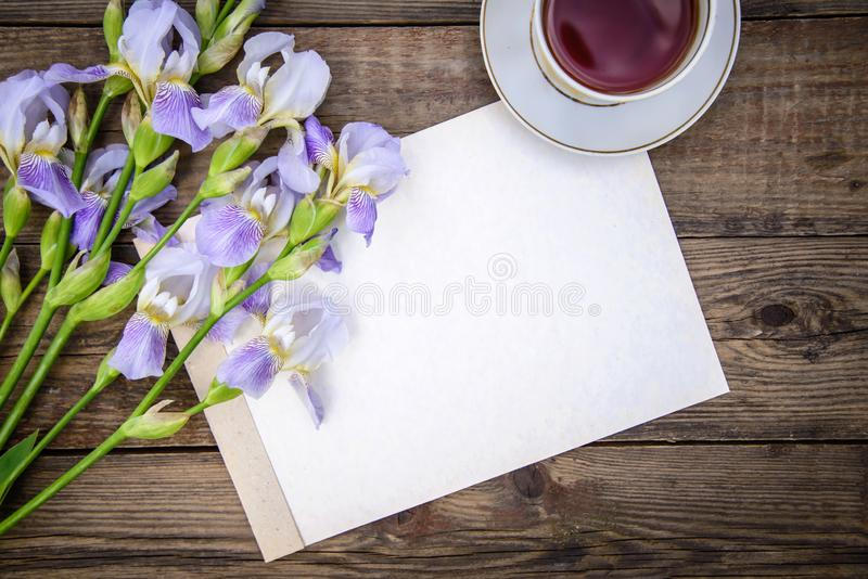 Beautiful purple flowers irises, a sheet of paper and a cup of tea on a wooden background. Beautiful purple flowers irises, a sheet of paper and a cup of tea on royalty free stock images