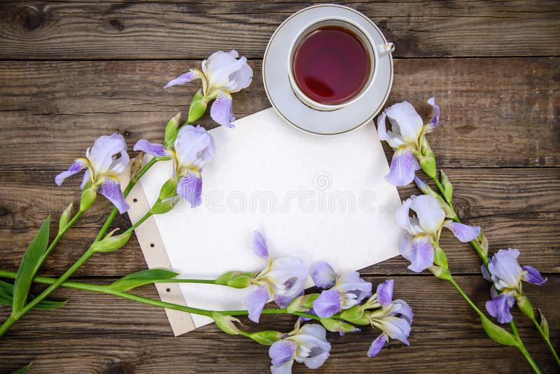Beautiful purple flowers irises, a sheet of paper and a cup of tea on a wooden background. Beautiful purple flowers irises, a sheet of paper and a cup of tea on stock photography