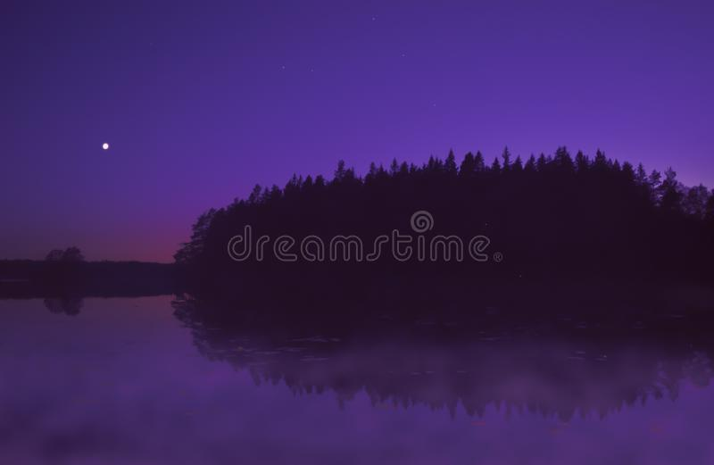 Beautiful purple sunset by lake in summer, with moon shining. Beautiful, colorful sunset/early night by a lake in summer. Moon shining. Forest reflecting in the