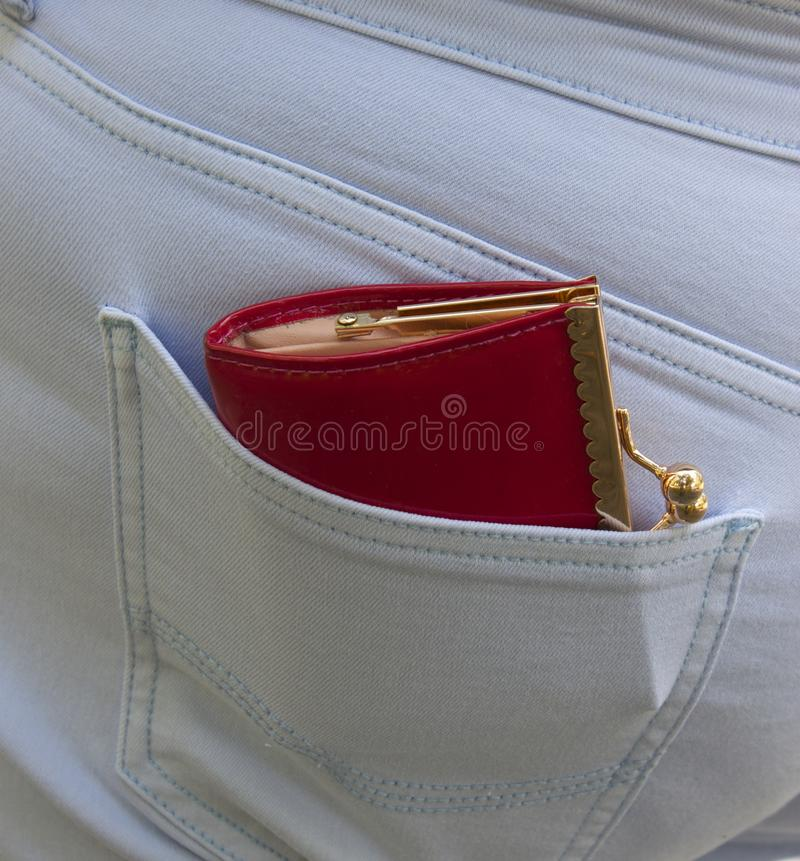 A beautiful purse with a gold fastener sticks out of a pocket of blue jeans. The concept of poverty or wealth. A beautiful red purse with a gold fastener sticks stock image