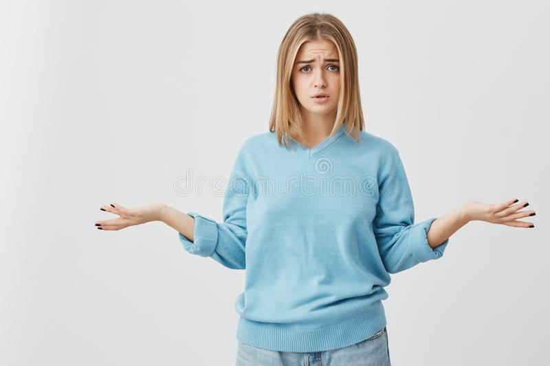 Beautiful puzzled and confused young woman dressed casually exclaming in despair and shrugging shoulders in full. Portrait of beautiful puzzled and confused royalty free stock image