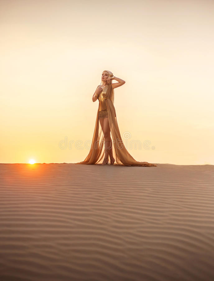 Beautiful queen of the desert. At sunset walks. Luxury golden dress and unusual jewelry. Gold flower in her hair, hairstyle with braids. Beautiful blonde royalty free stock image