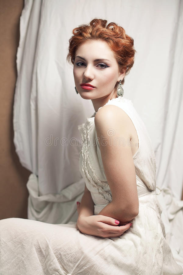 Beautiful queen like girl in bedroom. Vintage portrait of a beautiful queen like girl in bedroom. retro style. studio shot royalty free stock image