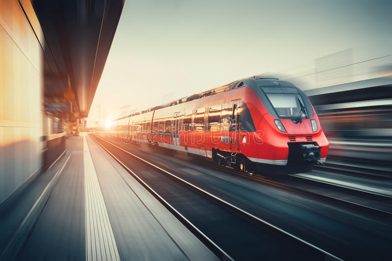 Beautiful railway station with modern red commuter train at suns. Beautiful railway station with modern high speed red commuter train with motion blur effect at stock photo