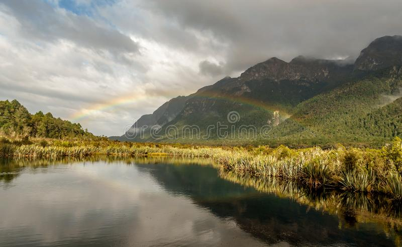 Beautiful Rainbow at Mountains of Milford Sound in New Zealand stock photography