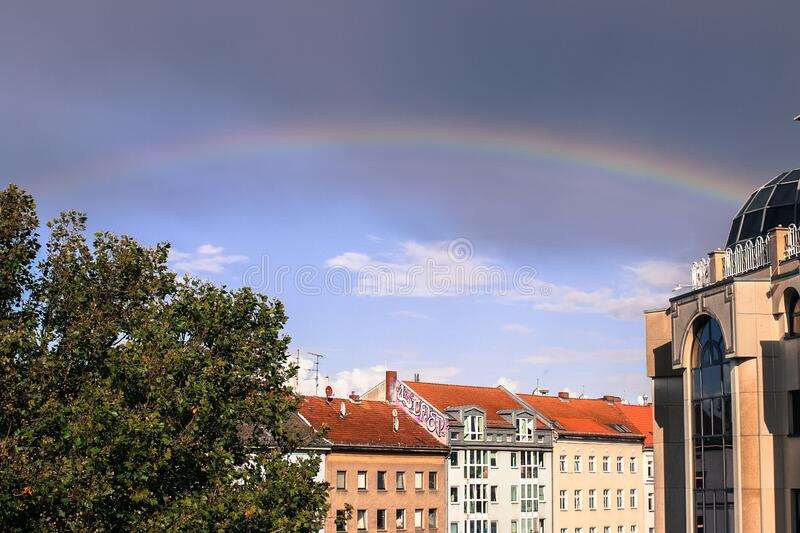 A beautiful rainbow after raining above the building with clouds stock photos