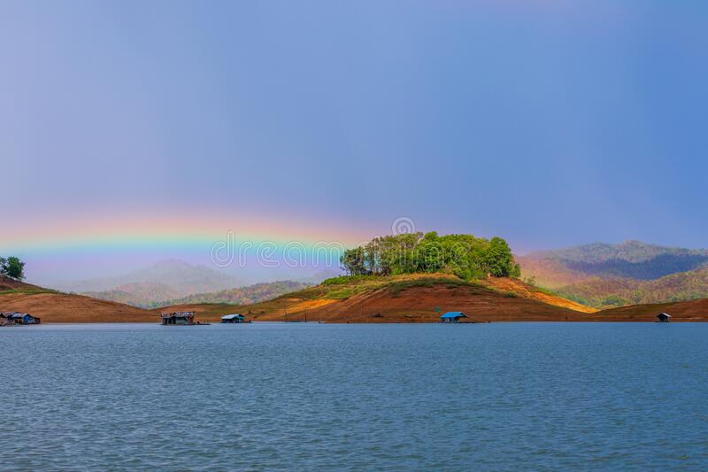 The beautiful rainbow show on rainy stop over the mountains and raft stock photography