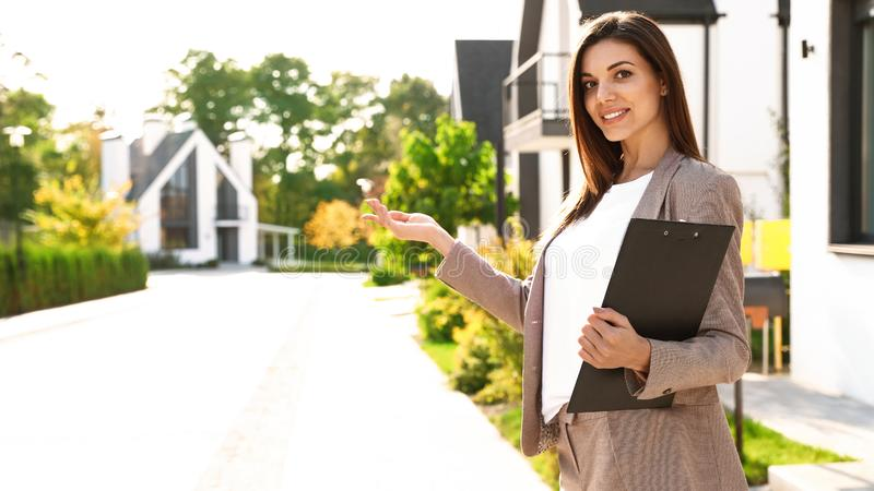 Beautiful real estate agent with documents royalty free stock image