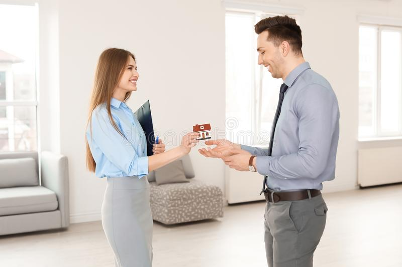 Beautiful real estate agent giving house model royalty free stock photos