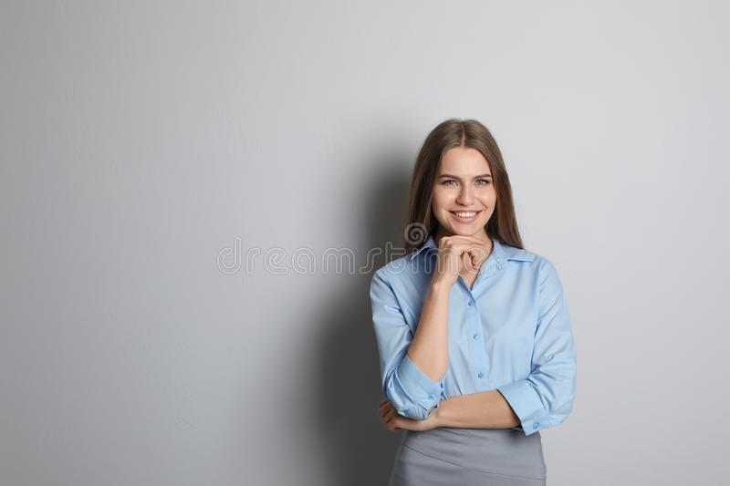 Beautiful real estate agent. On grey background royalty free stock photo