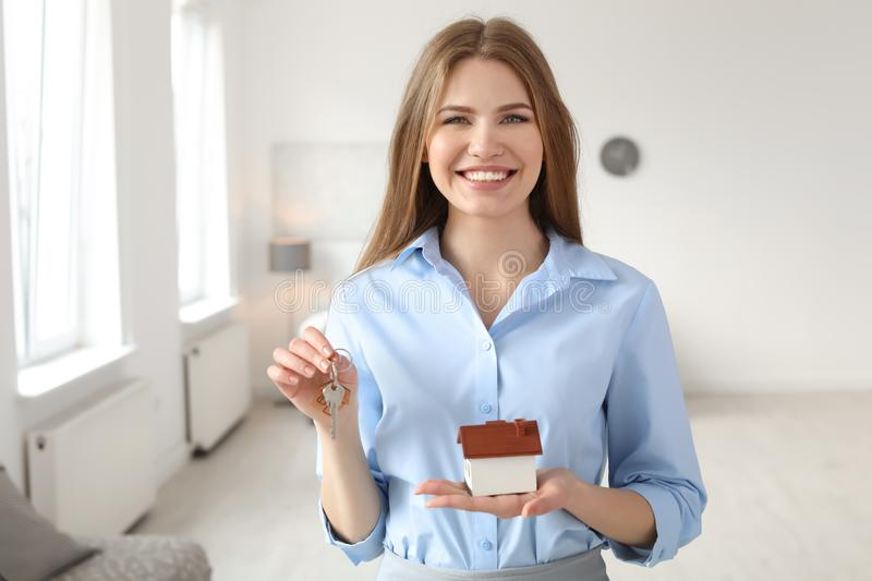 Beautiful real estate agent with house model and key stock photo