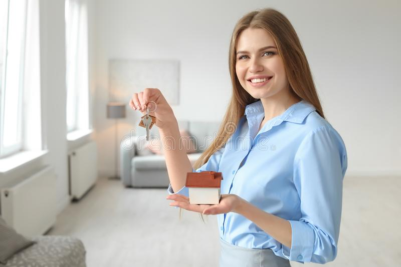 Beautiful real estate agent with house model and key stock photography