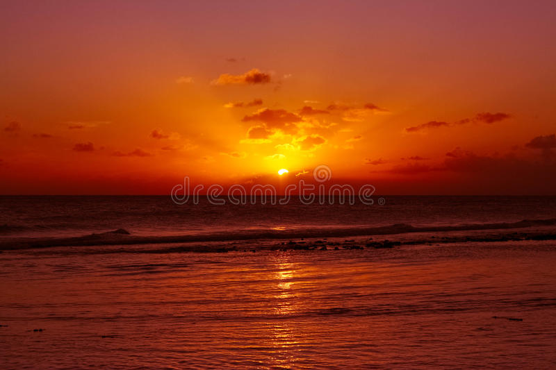 Beautiful Red Beach Sunset. Waves on a red sunset in warm caribbean sea royalty free stock photos
