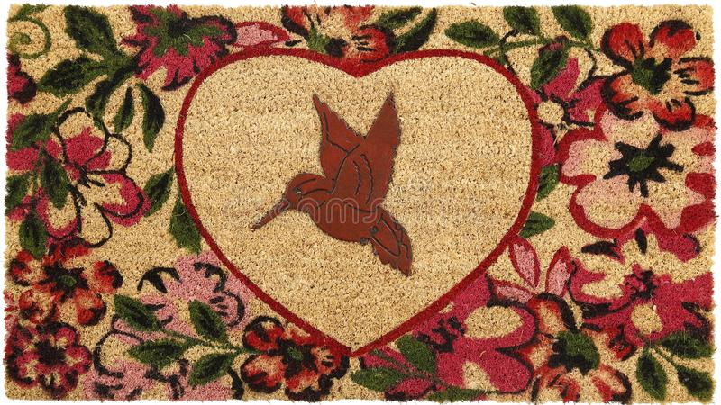 Beautiful red bird peach color coir doormat with heart shape flower border royalty free stock images