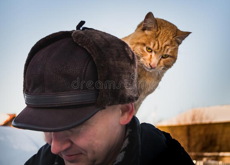 A beautiful red cat with yellow eyes sits on a back of a middle-aged man in a brown hat in winter royalty free stock photo