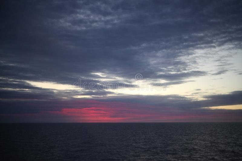 Beautiful red colorful sunrise at the sea with dramatic clouds and sun shining. Beautiful colorful sunrise at the sea with dramatic clouds and sun shining royalty free stock photography