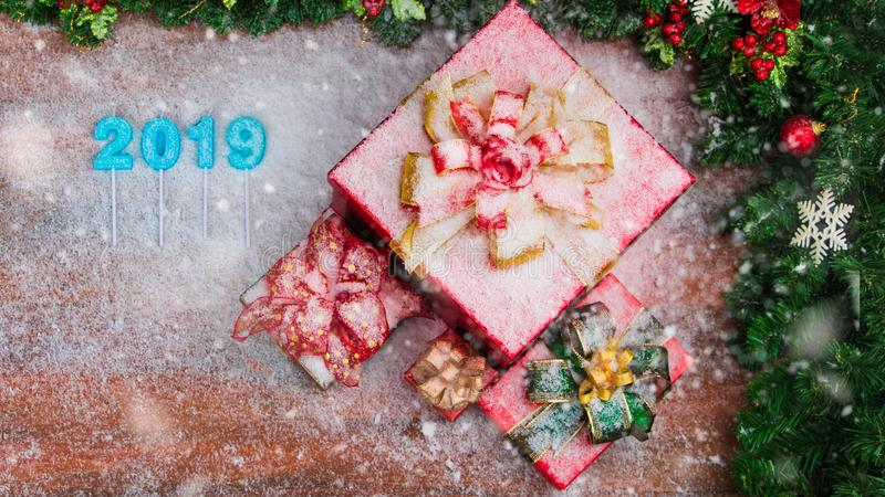Beautiful red gift boxes bordered with pine branches red ornaments, 2019 number in middle, copy space bottom left. Snow flake royalty free stock image