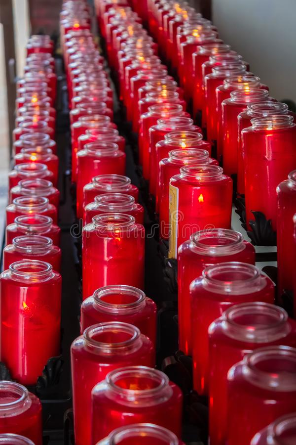Beautiful red glass prayer candles lined up in rows royalty free stock images