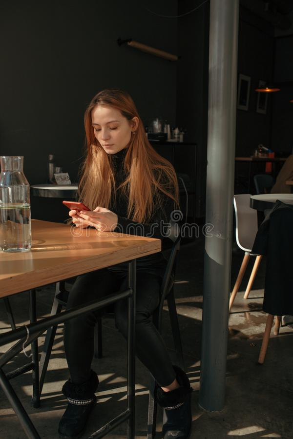 Beautiful red hair girl sitting in cafe in phone stock photos