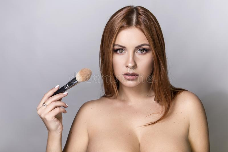 Beautiful red hair plus size model applying make up with a brush. On a neutral grey background. Flawless skin, fashion glamour portrait royalty free stock photos
