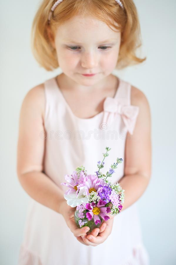 Beautiful red-haired child holding a bouquet of flowers royalty free stock photo