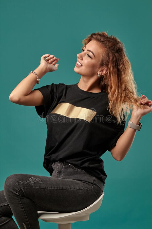 Ginger girl with a curly hair, wearing black t-shirt with a golden stripe is posing sitting on a chair against blue. Beautiful red-haired female with a curly royalty free stock image