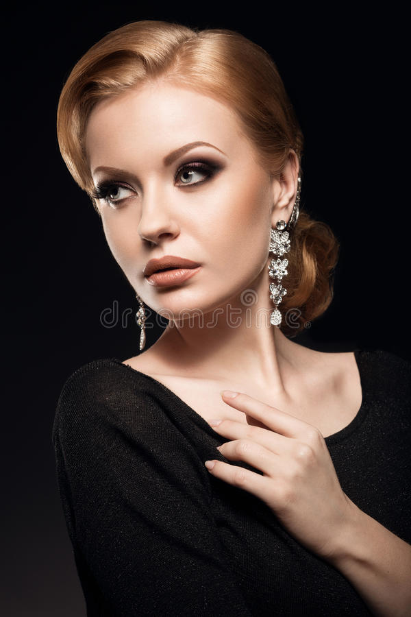 Beautiful red-haired girl in a black dress with a smooth evening haircut in the form of waves and bright makeup. Beauty face. Picture taken in the studio on a royalty free stock photo