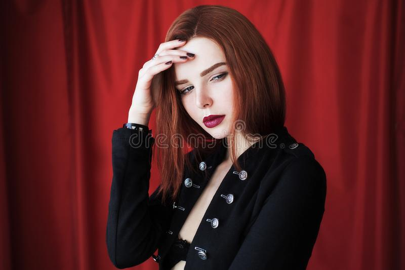 Beautiful red-haired girl with red lips on red background stock image