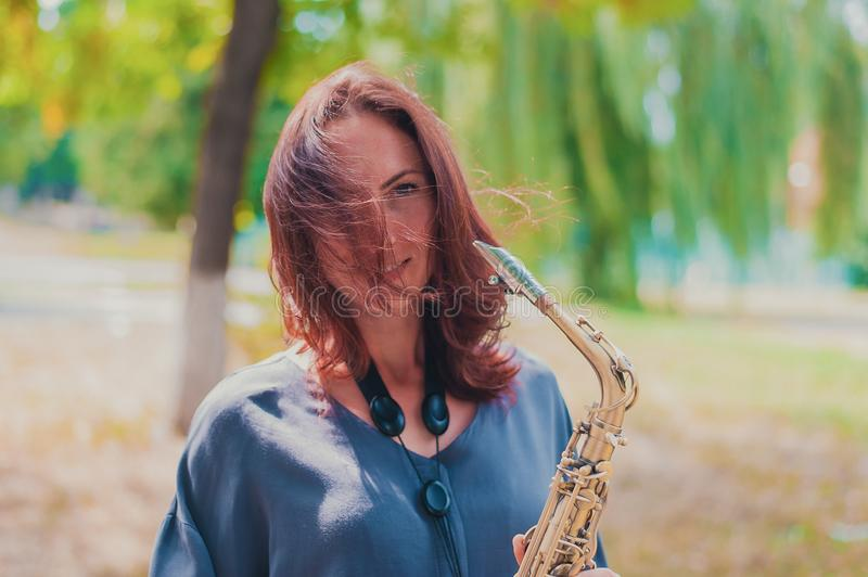 Beautiful red-haired girl in a blue jacket with a saxophone in windy weather royalty free stock images