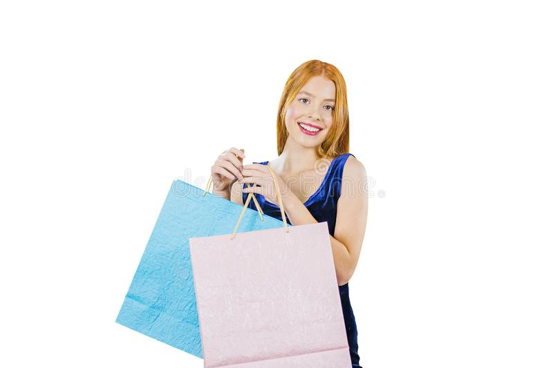 A beautiful red-haired girl in a blue velvet dress holding shopping bags in front of her and looking at the camera royalty free stock images