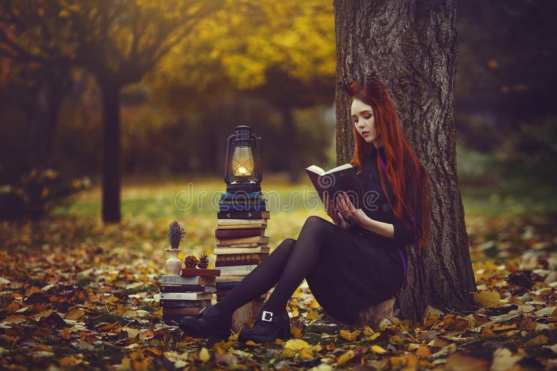 Beautiful red-haired girl with books and a lantern sitting under a tree in the autumn fairy forest. A fabulous autumn royalty free stock photography