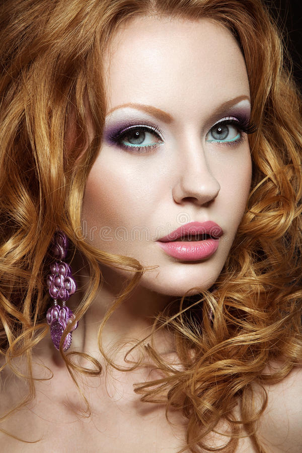 Beautiful red-haired girl with bright makeup and curls. stock images