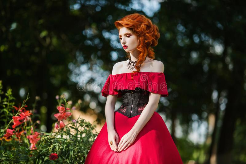 Beautiful red-haired girl in a red dress on a green background stock images