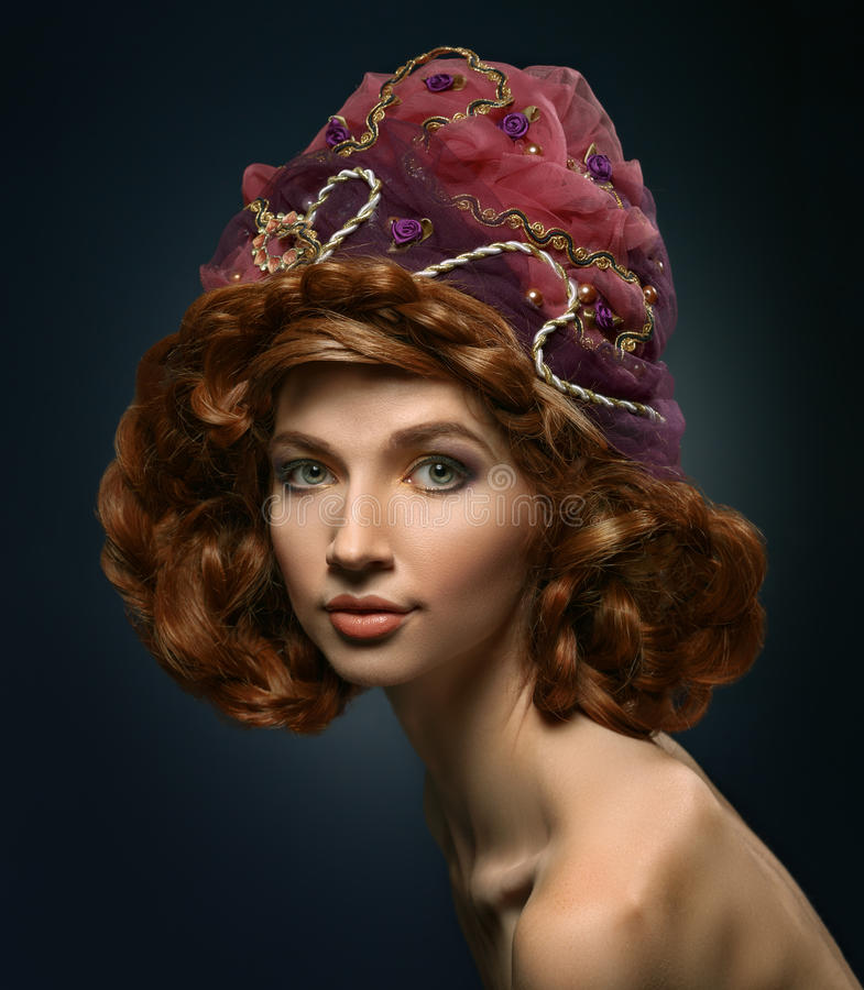 Beautiful red-haired girl in a headdress. Hair braided. Looking at the camera stock photography