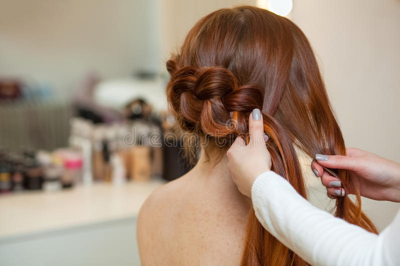 Beautiful, red-haired girl with long hair, hairdresser weaves a French braid, in a beauty salon. stock photo