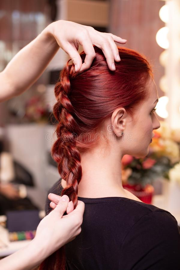 Beautiful, red-haired girl with long hair, hairdresser weaves a French braid, in a beauty salon. Professional hair care. And creating hairstyles royalty free stock image