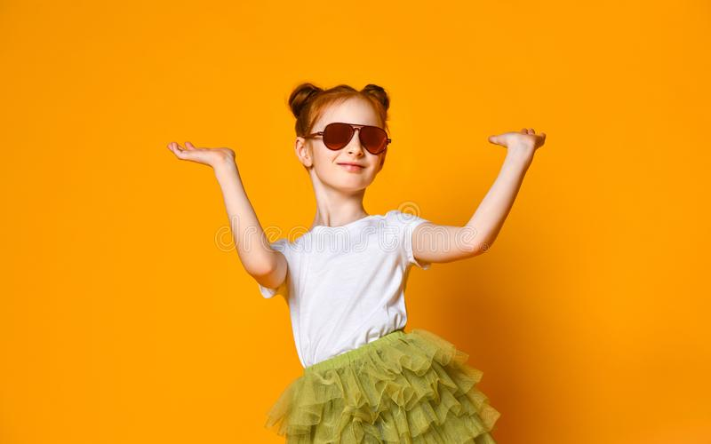 Beautiful red-haired girl in sunglasses rejoices spreading her arms to the sides. royalty free stock images