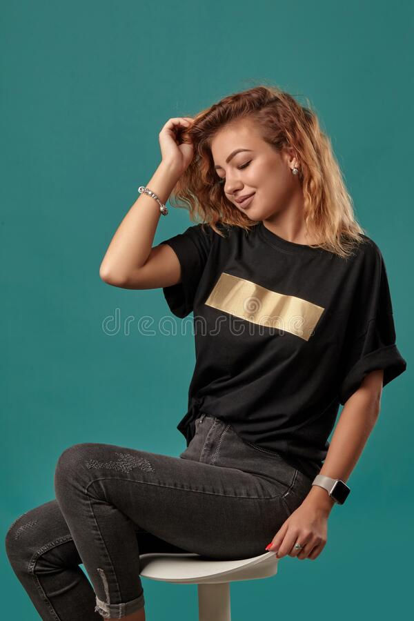 Ginger girl with a curly hair, wearing black t-shirt with a golden stripe is posing sitting on a chair against blue. Beautiful red-haired lady with a curly hair stock photos