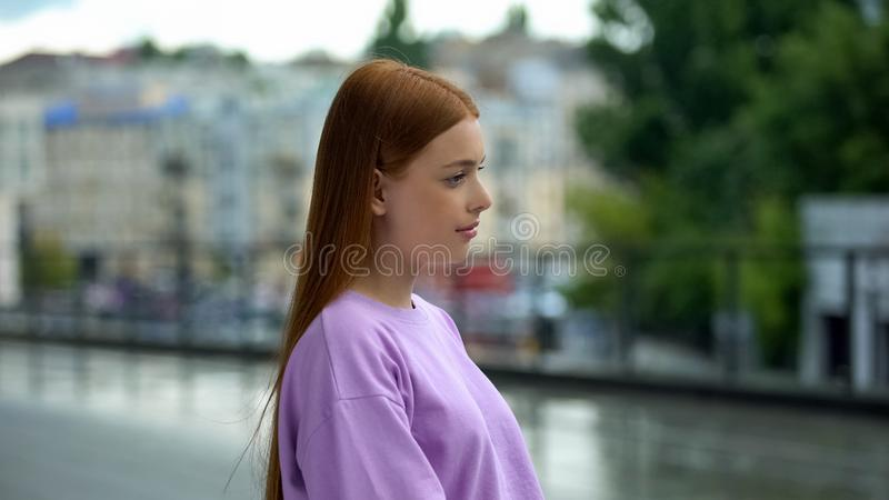 Beautiful red-haired teen girl standing alone on street, feeling melancholy. Stock photo stock photos