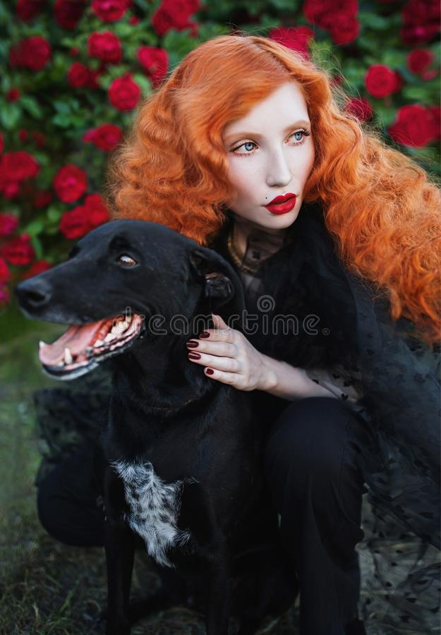 Beautiful red-haired woman with curly hair next to a black dog royalty free stock images