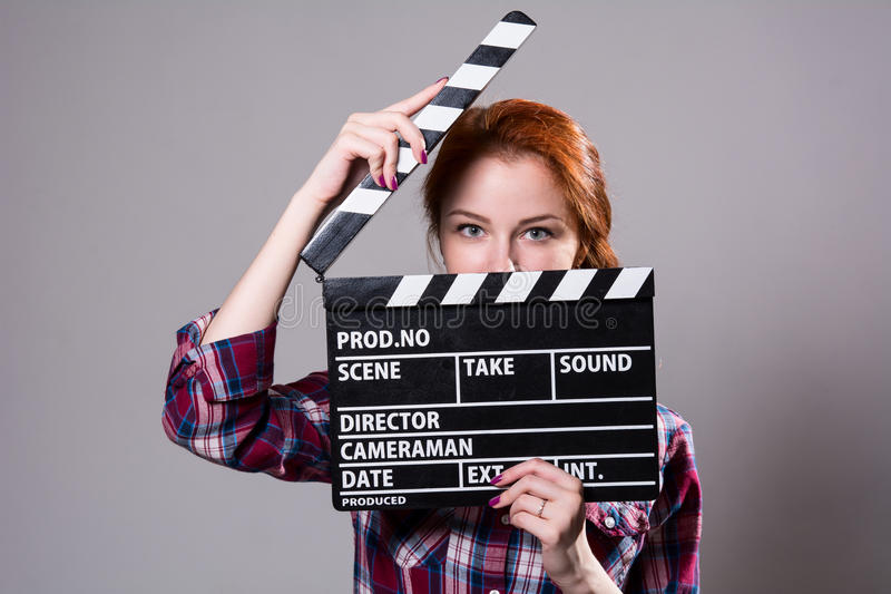 Beautiful red-haired woman holding a movie clapper, isolated over gray background royalty free stock photo