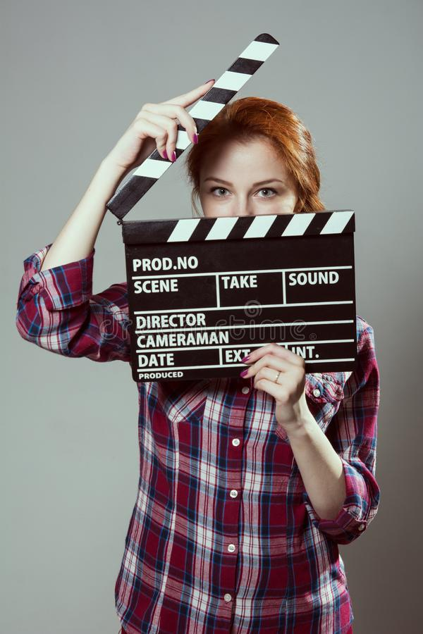 Beautiful red-haired woman holding a movie clapper, isolated over gray background. stock image