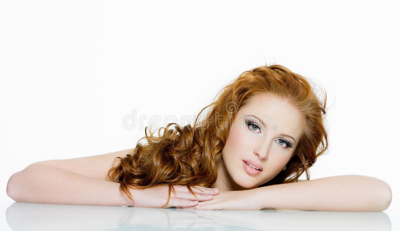 Beautiful red-haired woman with long wavy hairs stock image