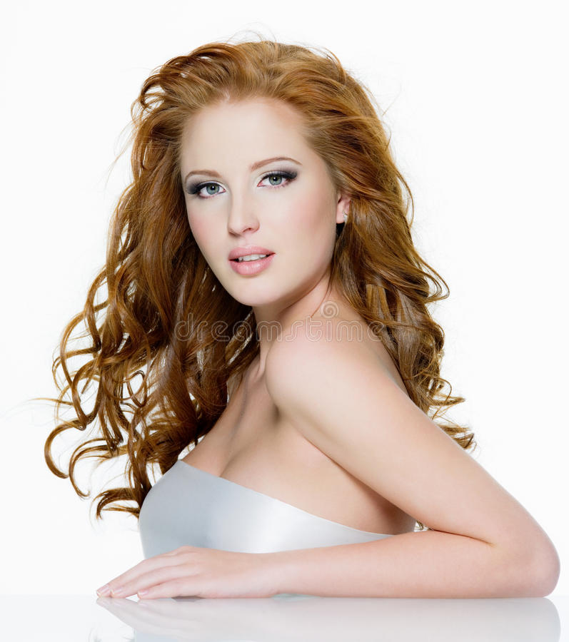 Beautiful red-haired woman with long wavy hairs. Beautiful sensual red-haired woman with long curly hairs - on white royalty free stock photography